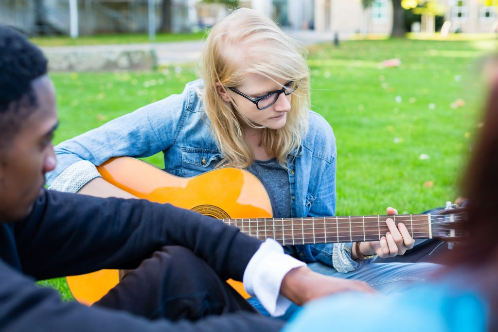 group of young people in park making music singings song and playing guitar