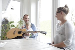 a family sitting at the table, making music with the guitar